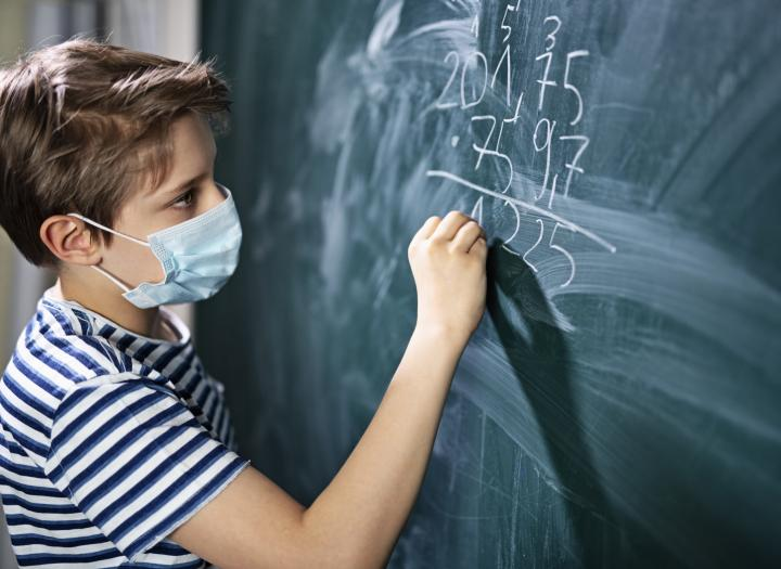 Young boy with mask does math problem on blackboard